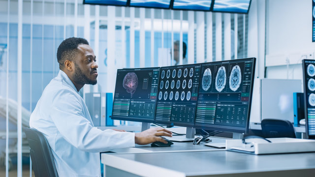 Medical Scientist Working with CT Brain Scan Images on a Personal Computer in Laboratory. Neurologists in Neurological Research Center Working on a Brain Tumor Cure.