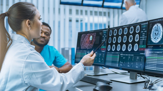 Medical Scientist and Surgeon Discussing CT Brain Scan Images on a Personal Computer in Laboratory. Neurologists / Neuroscientists in Futuristic Neurological Research Center