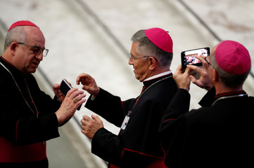 Bishops take pictures before Pope Francis' meeting with the youth and the Synod Fathers at the Paul VI Hall in Vatican