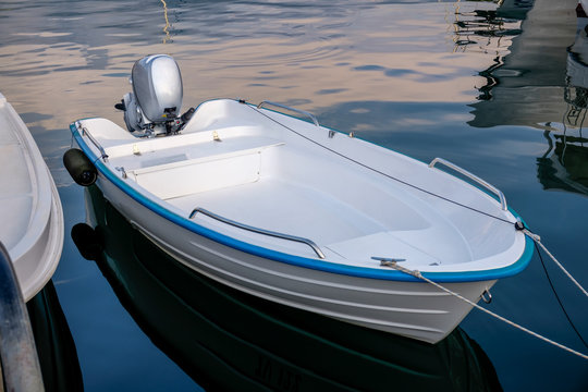Blue white power boat stops at the port  Small motor boat on a calm , silent sea Reflections  Motorized boat and sea at sunset