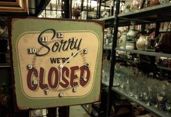 vintage sign indicating the closing time of a shop in a flea market