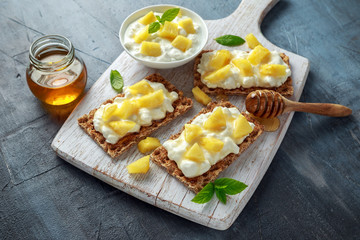 Homemade Crispbread toast with Cottage Cheese, Pineapple and honey on white wooden board.