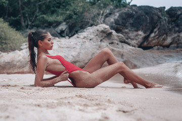 Young fit woman in red swimsuit siting  on the wet sand beach with out of focus rocks in background. Pulls hands swimsuit . Karon beach , Phuket