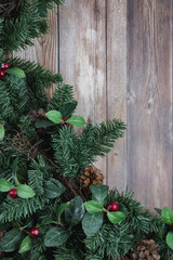 Christmas greenery with red berries lower left corner on rustic wood plank background