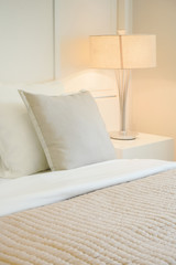 Beige pillow on comfy bed in modern interior bedroom