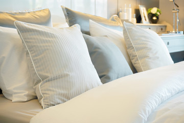Closeup roll of pillows setting on comfortable bed