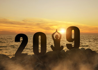 Silhouette of a girl practicing yoga on a cliff by the sea during the celebration New Year 2019.