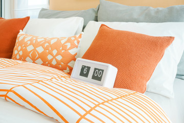 White alarm clock on bed with orange, white and gray pillows in background