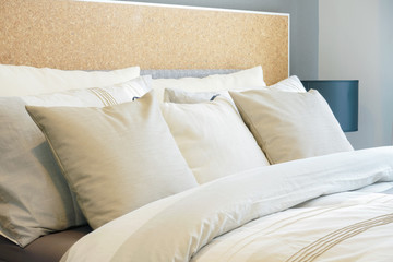 Closeup row of pillows on bed, beige color scheme bedding