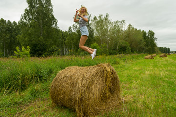A pretty blonde woman in a striped black and white T-shirt and denim shorts sits on a large round stack of dry hay collected on a summer or autumn afternoon against a background of green grass