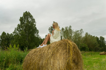A pretty blonde woman in a In a white knitted woolen jacket sits on a large round stack of dry hay collected on a summer or autumn day against a background of green grass at half a turn position