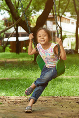 Asian girl on a swing playing at a park