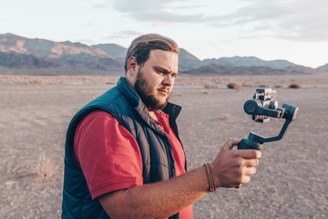 Young attractive man films a travel video using the  steadycam gimbal and an Phone