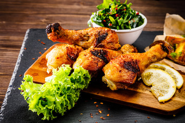 Grilled chicken drumsticks with baked potatoes and vegetable salad on wooden table