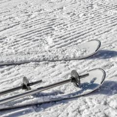 Background with white skis and ski poles on snow