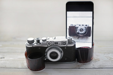 vintage camera and modern black smartphone on wooden light background, the concept of development and progress of photographic equipment and electronics