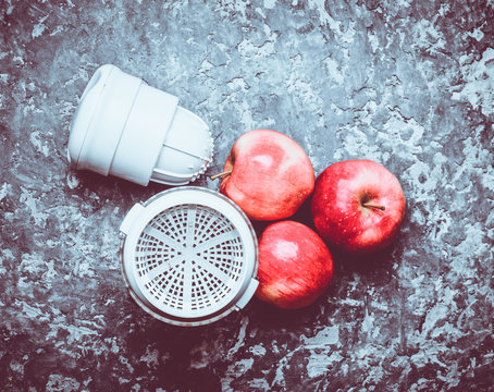 Hand juicer and apples on a concrete table. The concept of healthy food. The cooking process. Top view. Rustic and loft style.