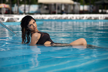 Fashion photo attractive slim woman with long dark hair in an elegant striped body swimsuit relaxing in a pool at a tropical resort. Wet girl posing lying in the water.
