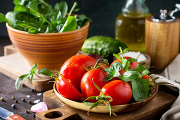 Healthy food: fresh vegetables on the kitchen table in a rustic style. Fresh tomatoes, cucumbers and rucola for cooking salad. Diet menu.