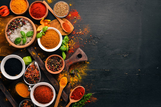 Spices and herbs on a wooden board. Pepper, salt, paprika, basil, turmeric. On a black wooden chalkboard. Top view. Free copy space.