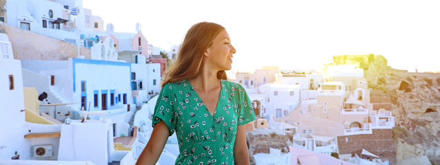 Young traveler woman visiting mediterranean village of Oia in Santorini Island. Panoramic banner picture of girl walking between typical white greek houses in Santorini.