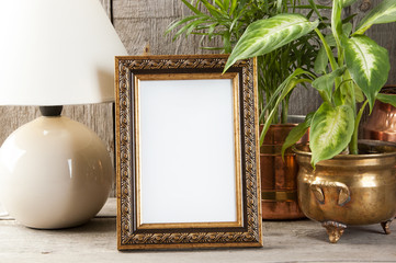 Empty brass picture frame on wooden background.