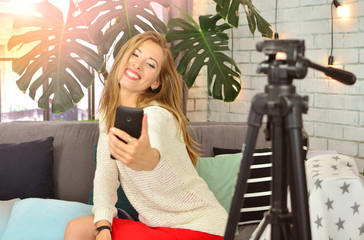 Beautiful girl blogger makes blog with smartphone at home.