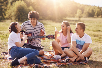 Summer, vacation, music and recreation time concept. Cheerful four friends or classmates have picnic outdoor, sing songs to guitar, drink energetic beverages, enjoys sunny warm day, pose on field
