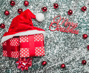 Red boxs and santa hat on a Christmas background. Winter holiday theme, space for text. Top view