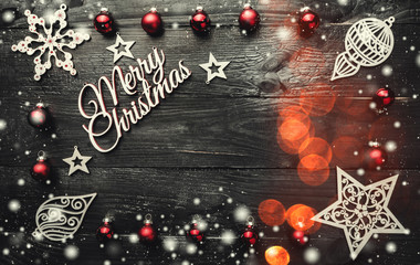 Merry Christmas greeting card. Xmas baubles, ornamented wooden toys and snowflakes, bokeh effect on a dark background