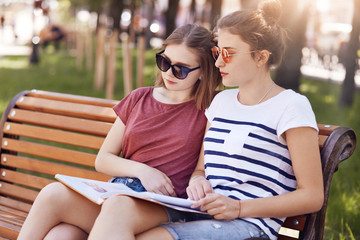 Female classmates sit closely to each other, read information from one book while sit on wooden bench, have focused expressions, dressed casually. Students prepare for upcoming final exam outdoor.