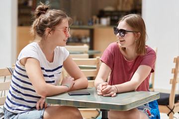 Indoor view of cheerful two pretty girls have lively conversation while wait for order in cafeteria, discuss thier summer rest, wear sunglasses, sit opposite each other. Recreation time concept.