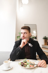 Portrait of a business man eating an appetizing salad in a cozy light restaurant and looking at the window. Man in a suit dishes with a salad in a cafe. Healthy food.