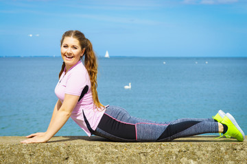 Woman doing yoga next to sea