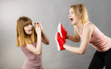 Agressive women fighting using shoes with female
