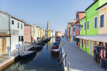 colorful rows of houses and boats of Burano island at sunny day, Venice, Italy