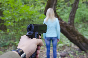 A terrorist holding a pistol, kidnapping young women hostage in the woods. Rape, terrorism, crime, rape, robbery and the killer concept of women.