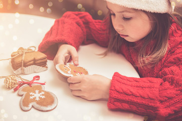 Little girl decorates gingerbread in Santa's red hat