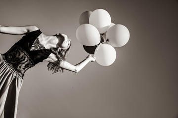 Redhead girl with colour balloons at blue sky background. Image in black and white style