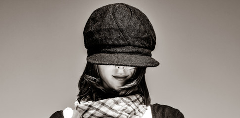 girl with scarf and purple cap on sky background. Image in black and white color style
