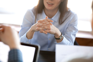 Smiling woman attentively listening to partners concentrated on business negotiations, nonverbal communication concept, focus on locked crossed fingers, clenched hands gesture close up view