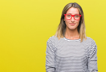 Young beautiful woman wearing glasses over isolated background with serious expression on face. Simple and natural looking at the camera.