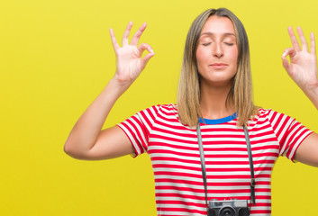 Young beautiful woman taking pictures using vintage photo camera over isolated background relax and smiling with eyes closed doing meditation gesture with fingers. Yoga concept.