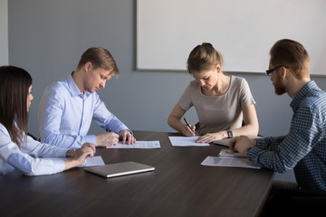 Businessman and businesswoman signing contracts concept filling form making agreement, partnership or collaboration deal at group meeting, new partners putting signature on business papers