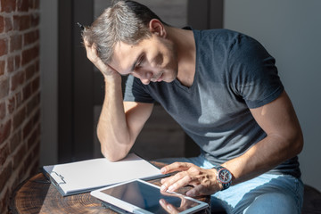 Serious man at the table with a tablet and a notebook, paying bills, business planning, work at home, startup