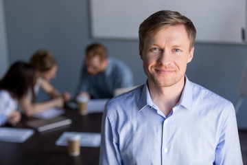 Head shot portrait of middle aged smiling successful business man, company ceo, leader, professional manager at office meeting, confident friendly male boss looking at camera with team at background