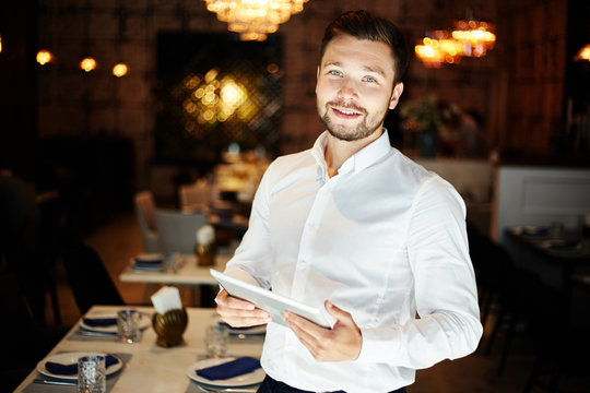 Smiling man with tablet in restaurant