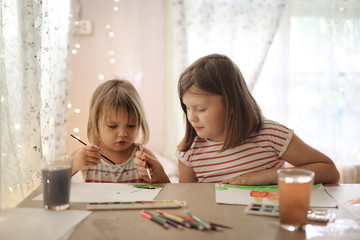 Children together paint with watercolors