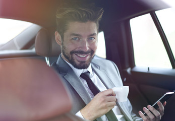 Businessman drinking coffee in car with phone in hand
