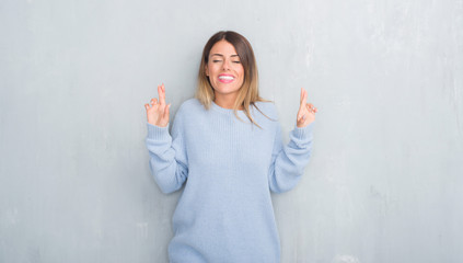 Young adult woman over grey grunge wall wearing winter outfit smiling crossing fingers with hope and eyes closed. Luck and superstitious concept.